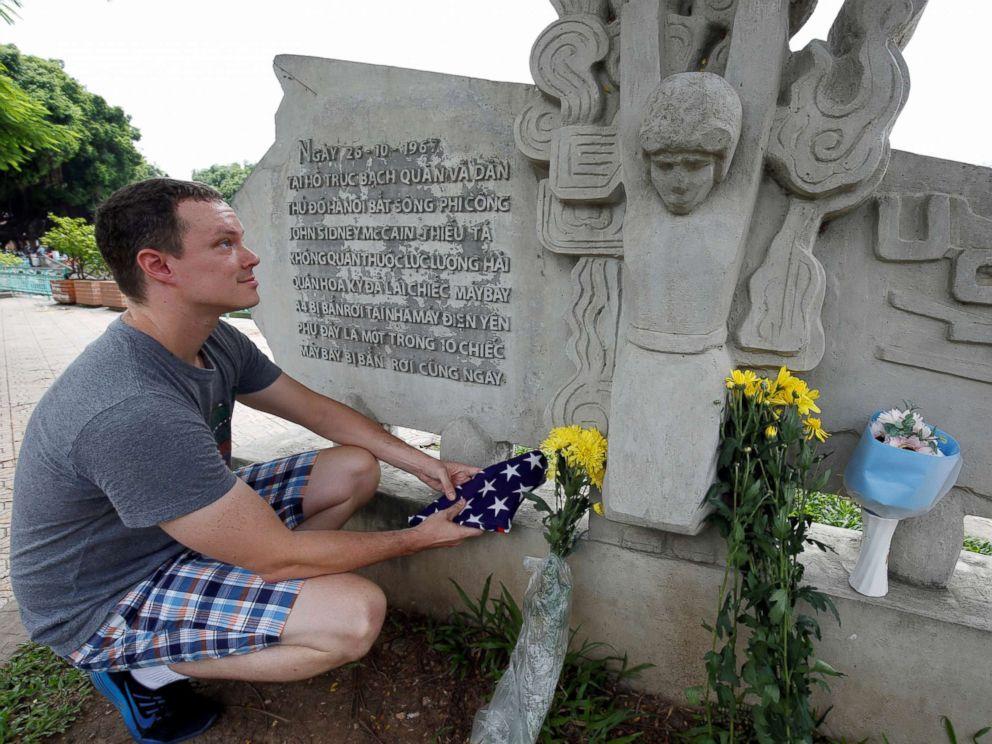 PHOTO: English teacher Derek Davis from the U.S. places an American flag and flowers in memory of the late Senator John McCain at the McCain Memorial in Hanoi, Vietnam, Aug. 26, 2018.
