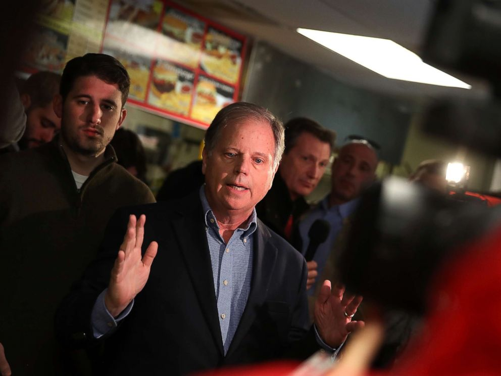 PHOTO: Doug Jones talks with reporters during a campaign stop at restaurant Chris Zs, Dec. 11, 2017, in Birmingham, Ala.