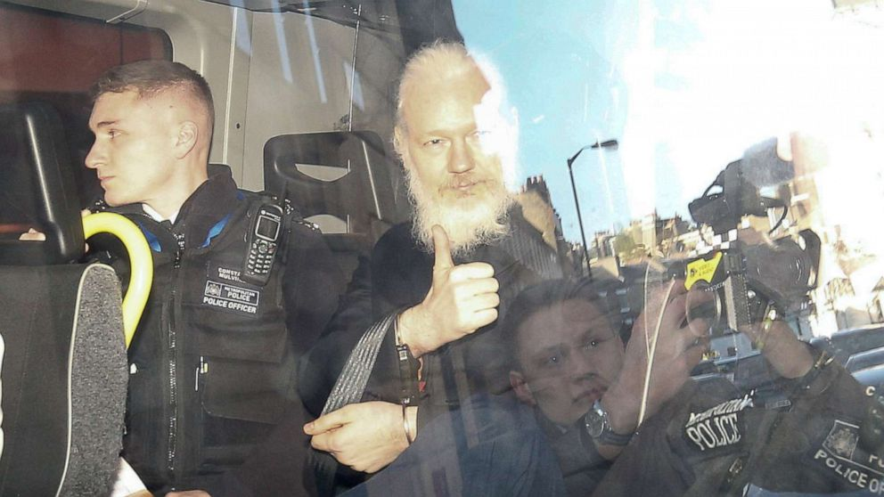 WikiLeaks founder Julian Assange gestures as he leaves the Westminster Magistrates Court in the police van, after he was arrested in London, April 11, 2019.