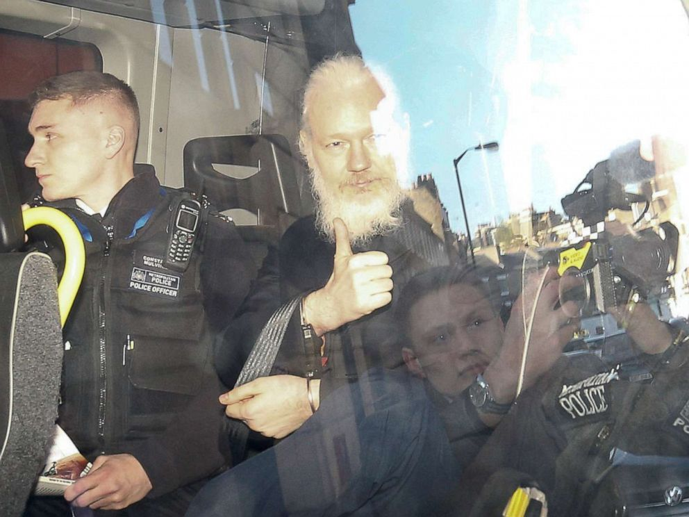 PHOTO: WikiLeaks founder Julian Assange gestures as he leaves the Westminster Magistrates Court in the police van, after he was arrested in London, April 11, 2019.