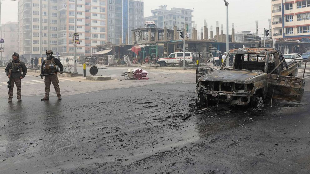 PHOTO: A charred vehicle sits in the road as Afghan security forces inspect the site of a bomb explosion in Kabul, Afghanistan, Dec. 20, 2020.
