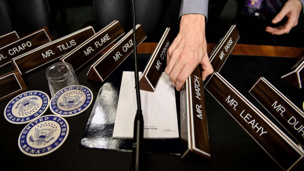 A staff member places name plates as the Senate Judiciary Committee's room  on Capitol Hill, Sept. 26, 2018 in Washington, during preparations one day before the hearing with Blasey Ford and Supreme Court nominee Judge Brett Kavanaugh.