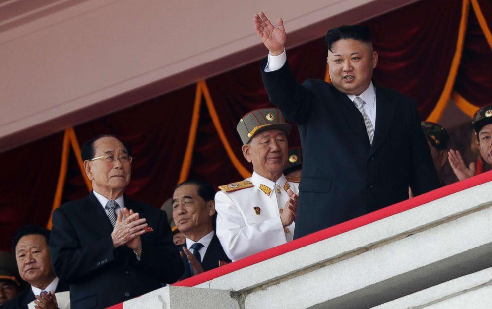 North Korean leader Kim Jong Un waves while officials, from left, Choe Ryong Hae, Kim Yong Nam, Pak Pong Ju, and Hwang Pyong So applaud during a military parade in Pyongyang, April 15, 2017.