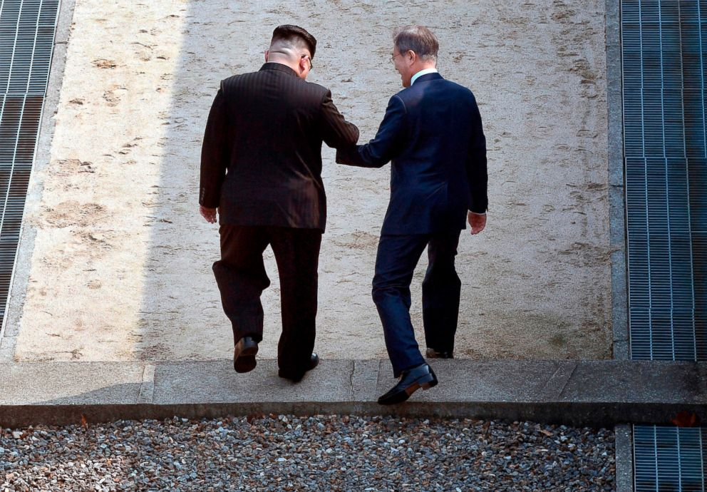 Kim Jong Un left and South Korean President Moon Jae-in cross the military demarcation line at the border village of Panmunjom in the Demilitarized Zone that divides the North and South