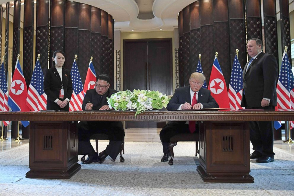 PHOTO: U.S. President Donald Trump (2nd R) and North Koreas leader Kim Jong Un (2nd L) sign documents as U.S. Secretary of State Mike Pompeo (R) and the North Korean leaders sister Kim Yo Jong (L), in Singapore, June 12, 2018.
