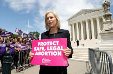 PHOTO: Presidential candidate and U.S. Senator Kirsten Gillibrand holds a protest sign in front of a crowd of abortion rights demonstrators during a rally outside the U.S. Supreme Court in Washington, D.C., May 21, 2019.