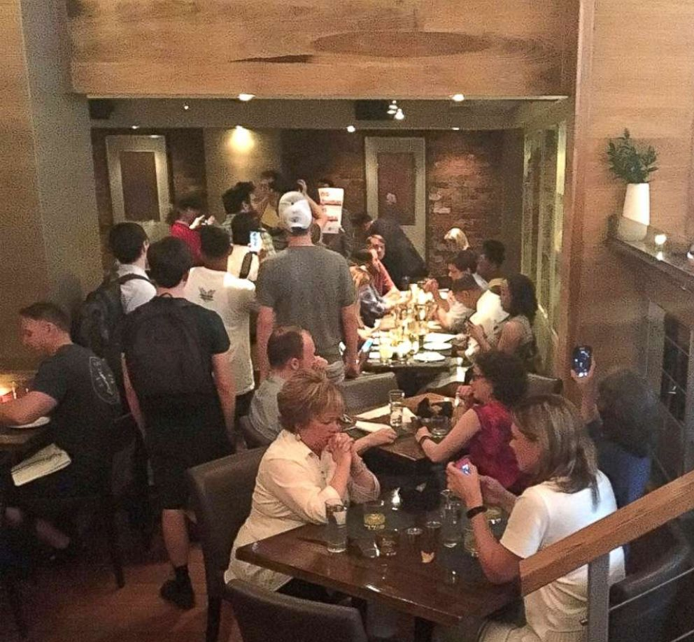 PHOTO: In this photo obtained from social media, activists chant slogans as they interrupt U.S. Homeland Security Secretary Kirstjen Nielsens (top R) dinner at a restaurant in Washington, D.C., June 19, 2018.