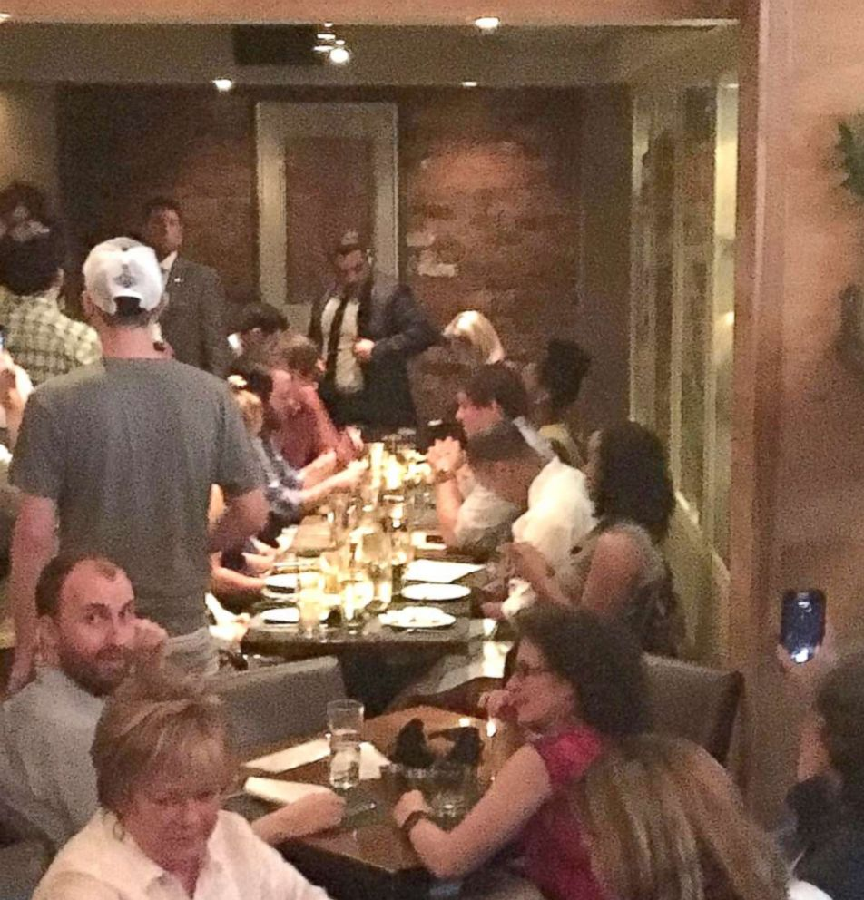 PHOTO: Activists chant slogans as they interrupt U.S. Homeland Security Secretary Kirstjen Nielsens (top R) dinner at a restaurant in Washington, D.C., June 19, 2018, in this photo obtained from social media.