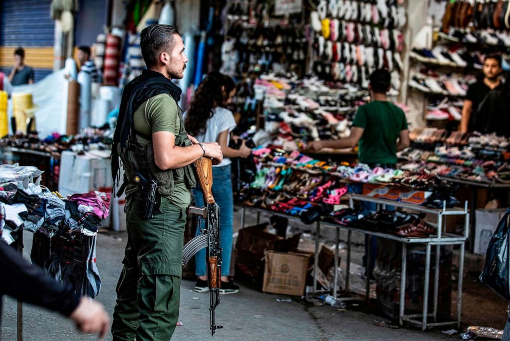 PHOTO: A member of the Kurdish Internal Security Police Force of Asayish stands guard at a market in the northeastern Syrian city of Qamishli on August 5, 2019.