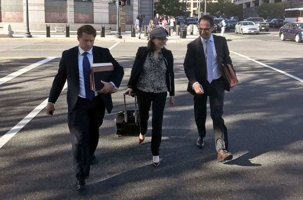 Kyle Freeny, center, walks with Andrew Weissman, right, as they leave court in Washington, Sept. 29, 2017.