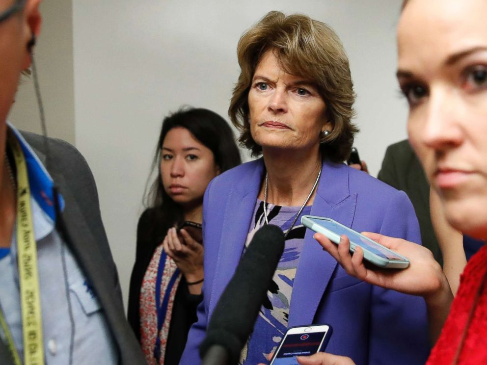 PHOTO: Sen. Lisa Murkowski walks on Capitol Hill, Oct. 3, 2018 in Washington, as reporters ask her questions.