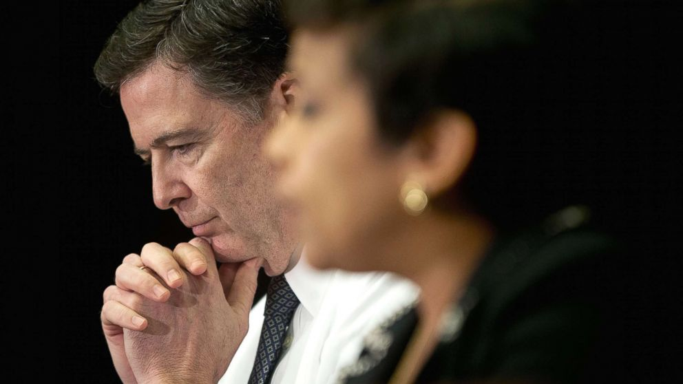 FBI Director James Comey listens at left as Attorney General Loretta Lynch speaks during a meeting with members of the media at Justice Department in Washington, D.C., Nov. 19, 2015.