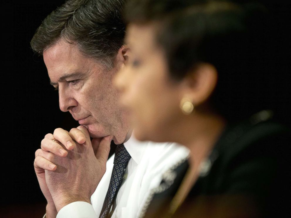 PHOTO: FBI Director James Comey listens at left as Attorney General Loretta Lynch speaks during a meeting with members of the media at Justice Department in Washington, D.C., Nov. 19, 2015.