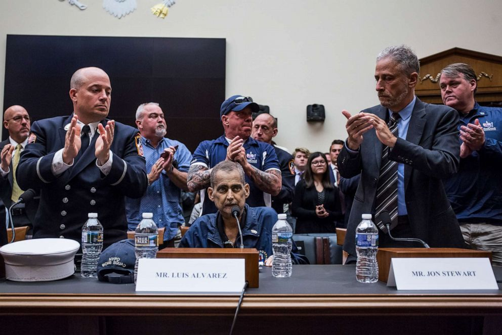 PHOTO: Michael OConnelll, left, John Feal, center, and Jon Stewart, right, applaud Luis Alvarez during a House Judiciary Committee hearing on reauthorization of the September 11th Victim Compensation Fund.