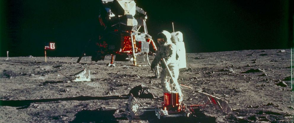 PHOTO: Aldrin is shown deploying the Passive Seismic Experiments Package on the lunar surface. The Lunar Module is in the background, together with the Laser Ranging Retro-Reflector.