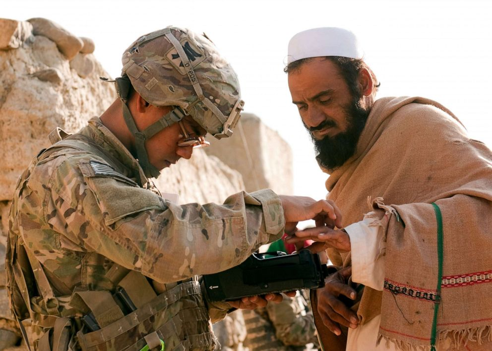 PHOTO:Army Pfc. Mark Domingo, takes an Afghan males fingerprints in the village of Dande Fariqan, Nov. 5, 2012.