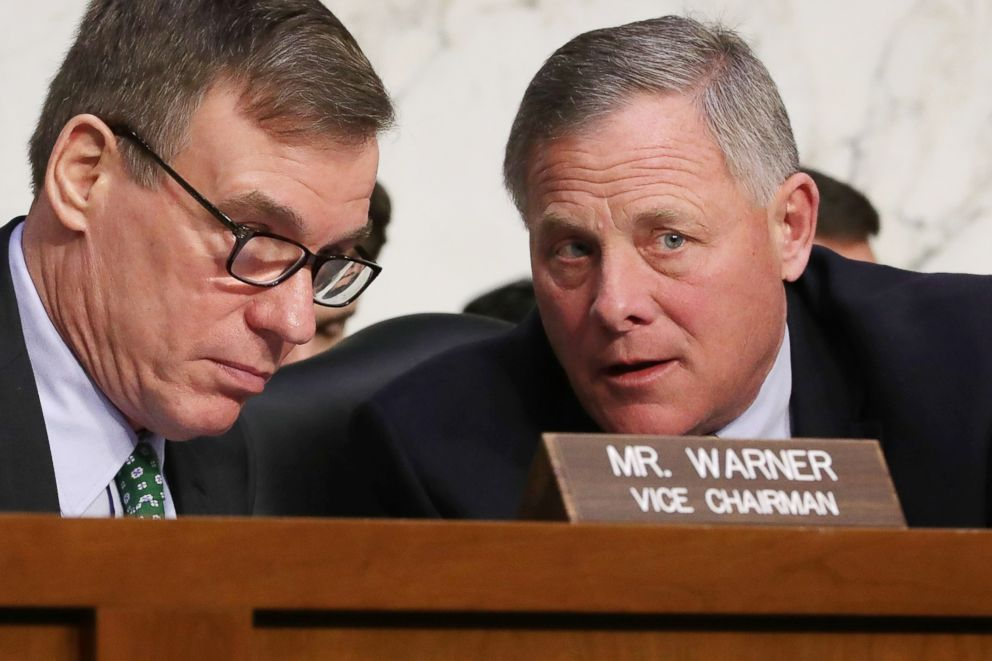 PHOTO: Senate Intelligence Committee ranking member Sen. Mark Warner (L) and Chairman Richard Burr confer during a committee hearing on Capitol Hill on March 21, 2018 in Washington.