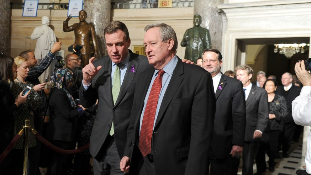 Senators Mark Warner (D-VA) left,, and Mike Crapo (R-ID) walk through Statuary Hall on Capitol Hill to attend President Trump's State of the Union address, Jan. 30, 2018.