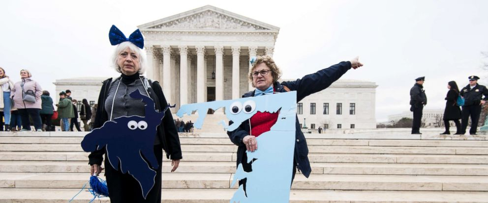 PHOTO: Gerrymandering activists Helenmary Ball, posing as MD district 5, and Rachael Lemberg, posing as MD district 1, gather on the steps of the Supreme Court as the court prepares to hear Benisek v. Lamone on March 28, 2018.