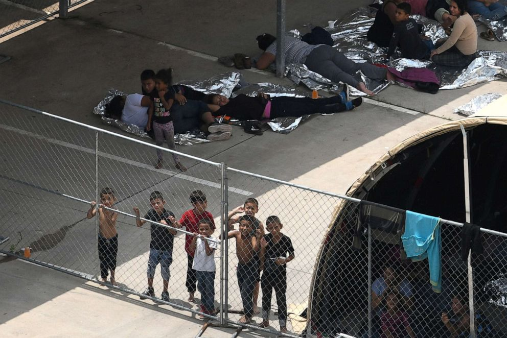 PHOTO: At a nearby facility to the Central Processing Center where a suspected flu outbreak has prompted officials to stop processing, migrants look out from a makeshift encampment at the U.S. Border Patrol McAllen Station in McAllen, Texas, May 15, 2019.