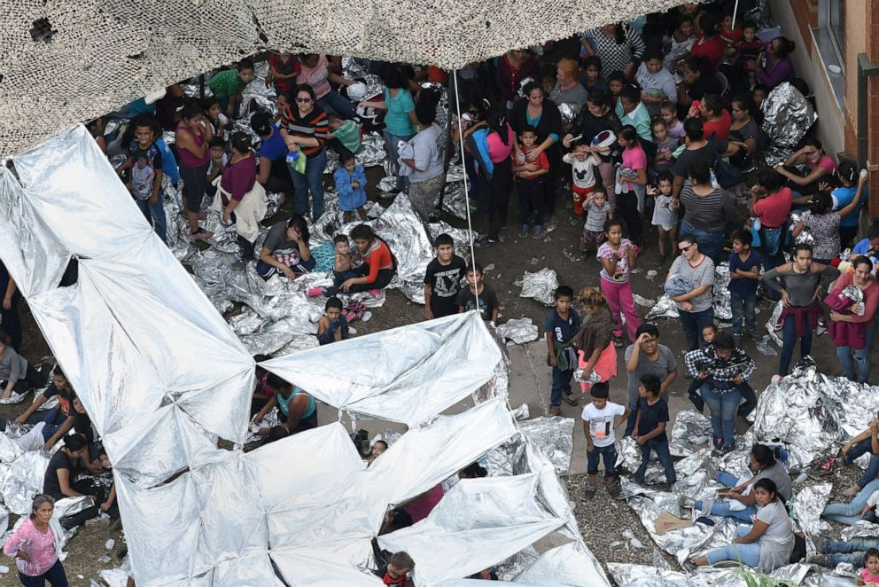 PHOTO: Migrants wait outside a makeshift encampment at the U.S. Border Patrol facility in McAllen, located close to the Central Processing Center where a suspected flu outbreak has prompted officials to stop processing, in McAllen, Texas, May 15, 2019.