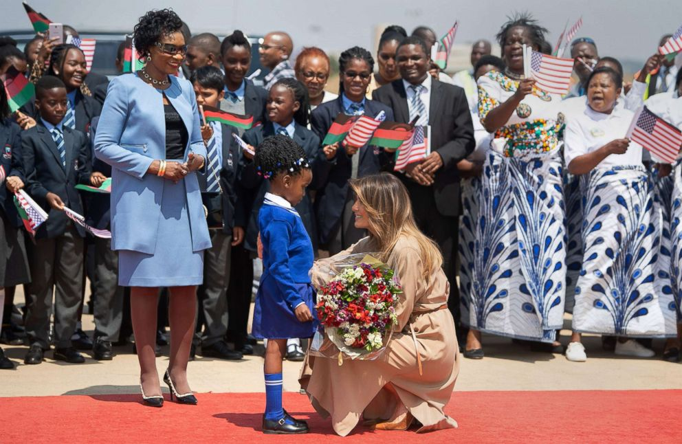 PHOTO: First lady Melania Trump receives flowers from a young girl alongside the first lady of Malawi, Gertrude Mutharika, left, upon her arrival at Lilongwe International Airport, Oct. 4, 2018 as part of her week long trip to Africa.