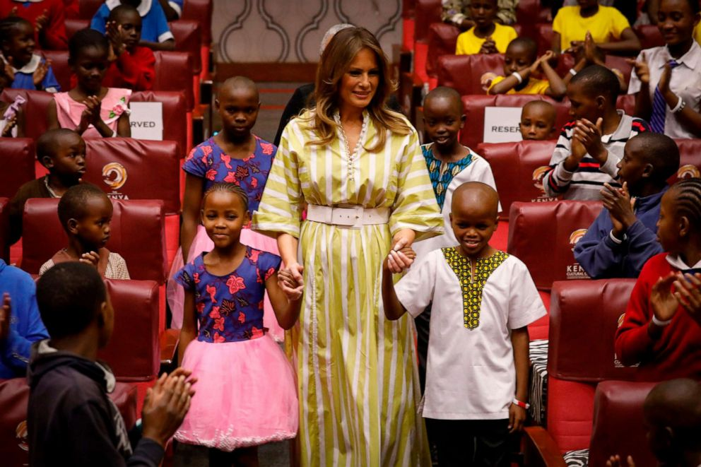 PHOTO: First lady Melania Trump smiles as she holds hands with Kenyan children upon her arrival at the Kenya National Theatre in Nairobi, Oct. 5, 2018.