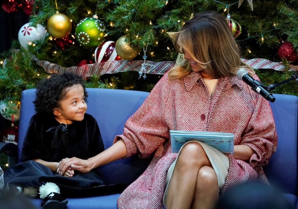 PHOTO: First lady Melania Trump reaches out to Tearrianna Cooke-Starkey while reading a childrens Christmas story during her visit to Childrens National Health System in Washington, DC, Dec. 13, 2018.
