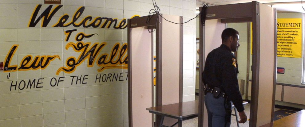 PHOTO: Police Officer Jeff Tatum passes through a metal detector at Lew Wallace High School March 30, 2001 in Gary, In.