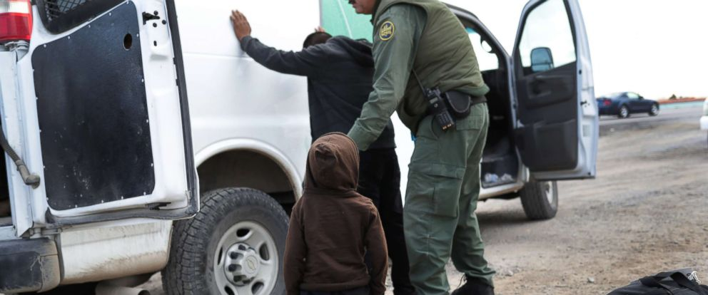 PHOTO: A child watches as a U.S. Border Patrol agent searches a fellow Central American migrant after they crossed the border from Mexico on Feb. 01, 2019, in El Paso, Texas.