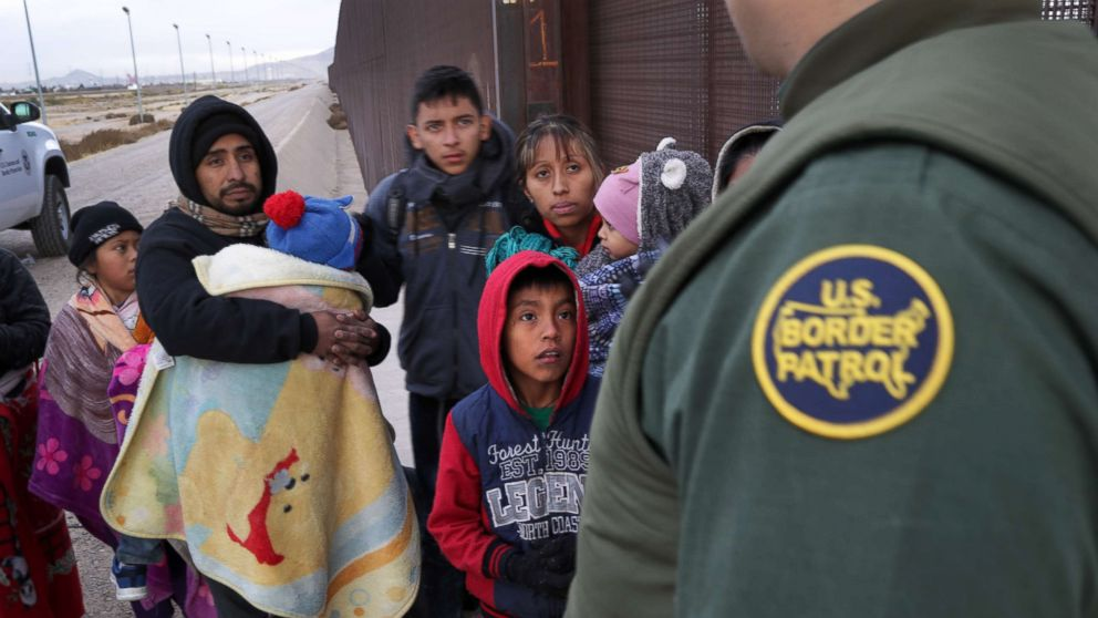 A U.S. Border Patrol agent speaks with Central American immigrants at the U.S.-Mexico border fence on Feb. 01, 2019, in El Paso, Texas.