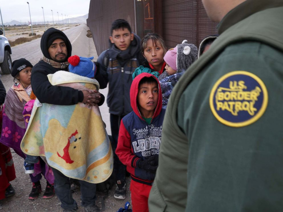PHOTO: A U.S. Border Patrol agent speaks with Central American immigrants at the U.S.-Mexico border fence on Feb. 01, 2019, in El Paso, Texas.