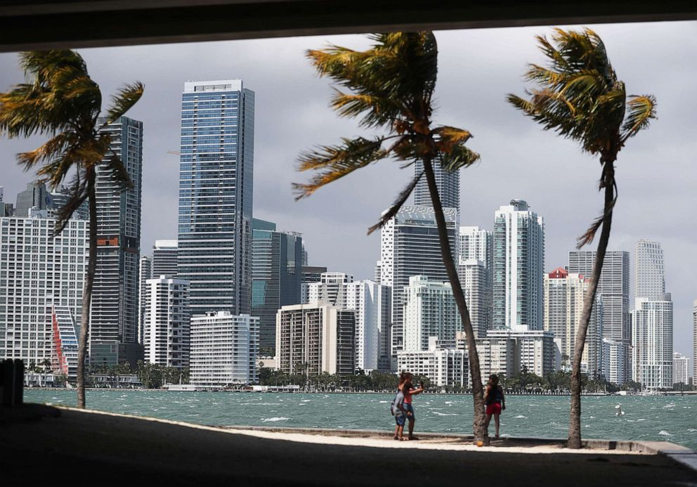 PHOTO: People take photos in front of the Miami skyline on March 28, 2019.