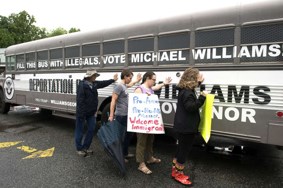 PHOTO: Protesters pray as they lay hands on the Deportation Bus of Georgia Republican Michael Williams during what Williams called his Deportation Tour of Georgia towns, May 16, 2018.