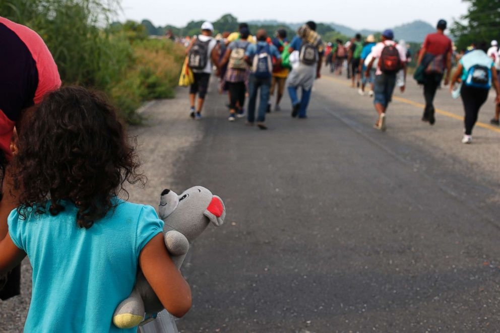 PHOTO: A girl carries a stuffed teddy bear as she walks with her mother with a migrant caravan near Arriaga, Chiapas state, Mexico, Oct. 27, 2018.