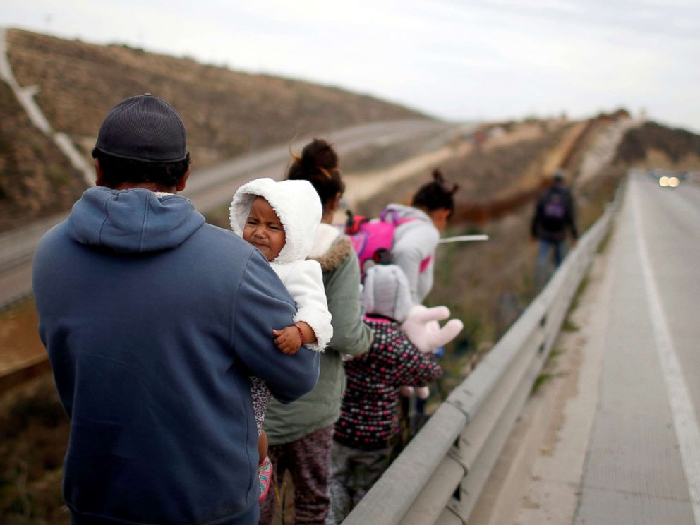 PHOTO: Migrants from Honduras, part of a caravan of thousands from Central America trying to reach the United States, walk next to the border fence as they prepare to cross it illegally in Tijuana, Mexico, Dec. 14, 2018.