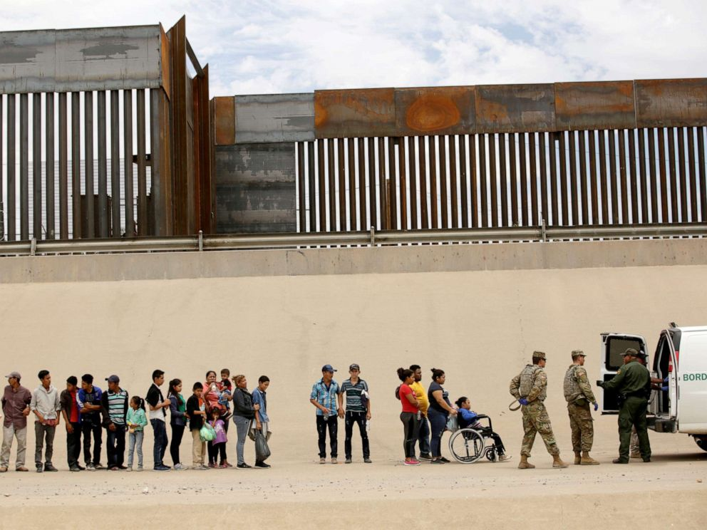 PHOTO: Members of the Border Patrol and U.S. Military help a migrant woman in a wheelchair as she and others migrants illegally crossed the border between Mexico and the U.S. to request political asylum, as seen from Ciudad Juarez, Mexico, July 6, 2019.