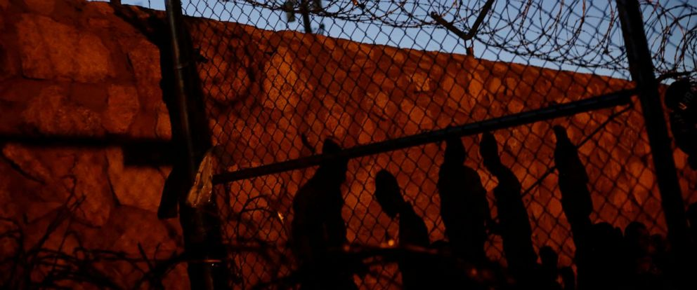 PHOTO: Central American migrants cast their shadows against a wall while inside an enclosure where they are being held by U.S. Customs and Border Protection (CBP), after crossing the border in El Paso, Texas, March 28, 2019.