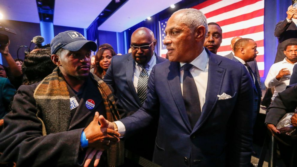 Democrat Mike Espy, right, who sought to unseat appointed U.S. Sen. Cindy Hyde-Smith, R-Miss., shakes hands with a supporter in a crowded auditorium at the Mississippi Civil Rights Museum in Jackson, Miss., after losing the runoff election, Tuesday night, Nov. 27, 2018.
