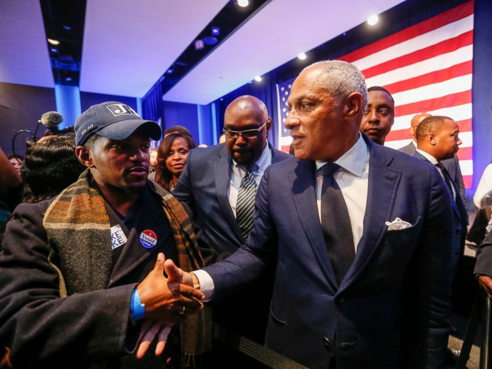 Democrat Mike Espy, right, who sought to unseat U.S. Sen. Cindy Hyde-Smith, R-Miss., shakes hands with a supporter in a crowded auditorium at the Mississippi Civil Rights Museum in Jackson, Miss., after losing the runoff election Tuesday, Nov. 27, 2018.