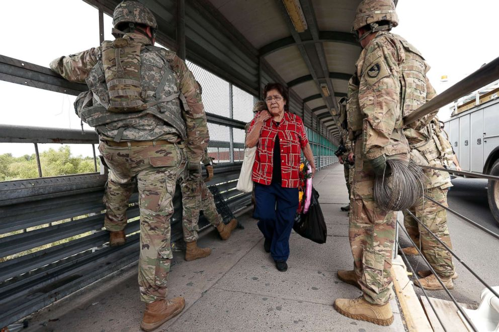 PHOTO: Pedestrians pass members of the U.S.military working to place razor wire along the U.S.-Mexico border on the McAllen-Hidalgo International Bridge, Nov. 2, 2018, in McAllen, Texas.