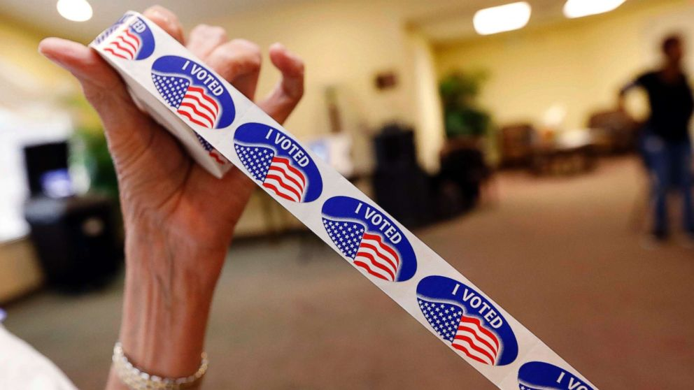 """Madison County election bailiff Shirley Lewis unrolls several """"I Voted"""" stickers that they give to each person who votes in their respective party in the Mississippi primary, June 5, 2018, in Madison, Miss."""