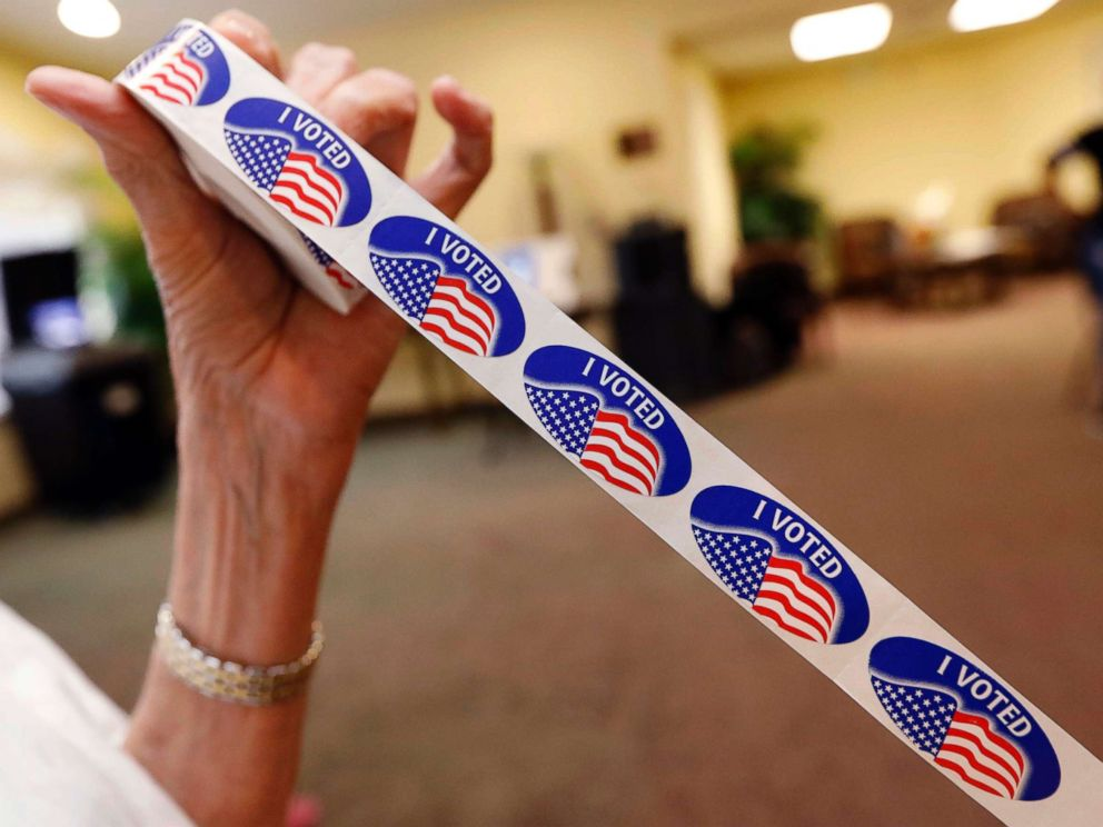 PHOTO: Madison County election bailiff Shirley Lewis unrolls several I Voted stickers that they give to each person who votes in their respective party in the Mississippi primary, June 5, 2018, in Madison, Miss.