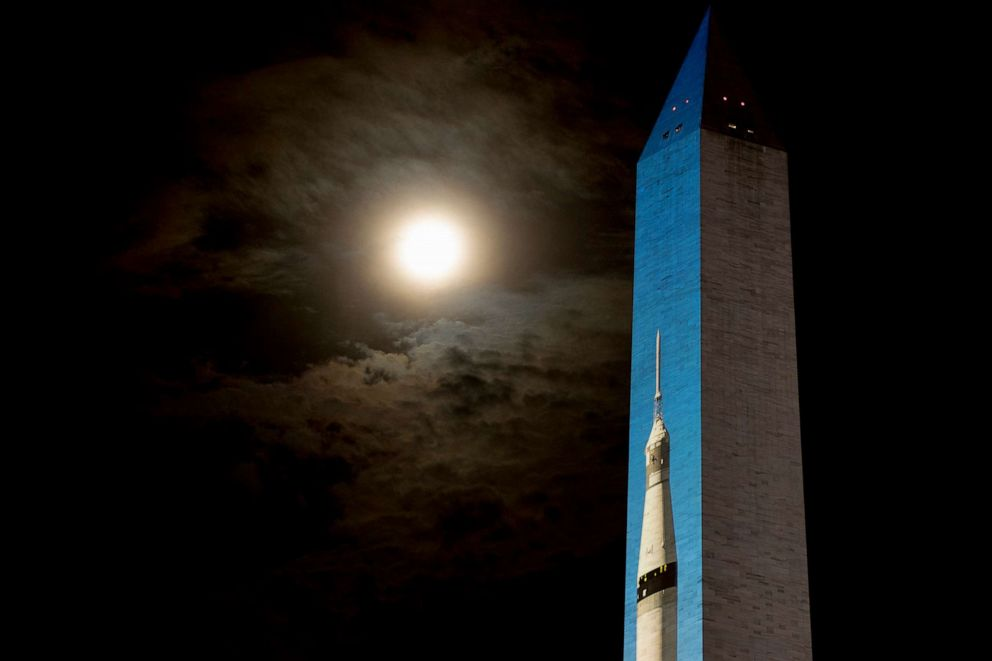 PHOTO: The moon is visible through clouds, left, as an image of a 363-foot Saturn V rocket is projected on the east face of the Washington Monument in Washington, July 17, 2019, in celebration of the 50th anniversary of the Apollo 11 moon landing.