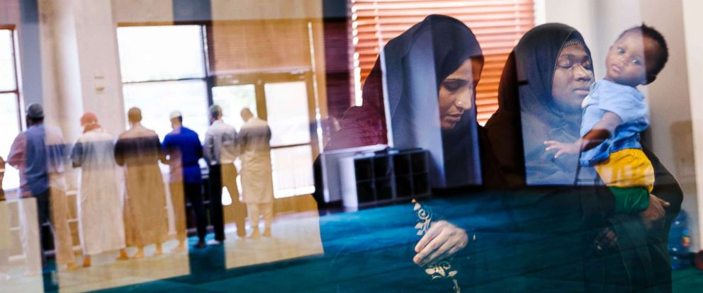 PHOTO: A boarded-up entry is reflected as Muslim women attend afternoon prayers at the North Austin Muslim Community Center on Sept. 4, 2018 in Austin, Texas.