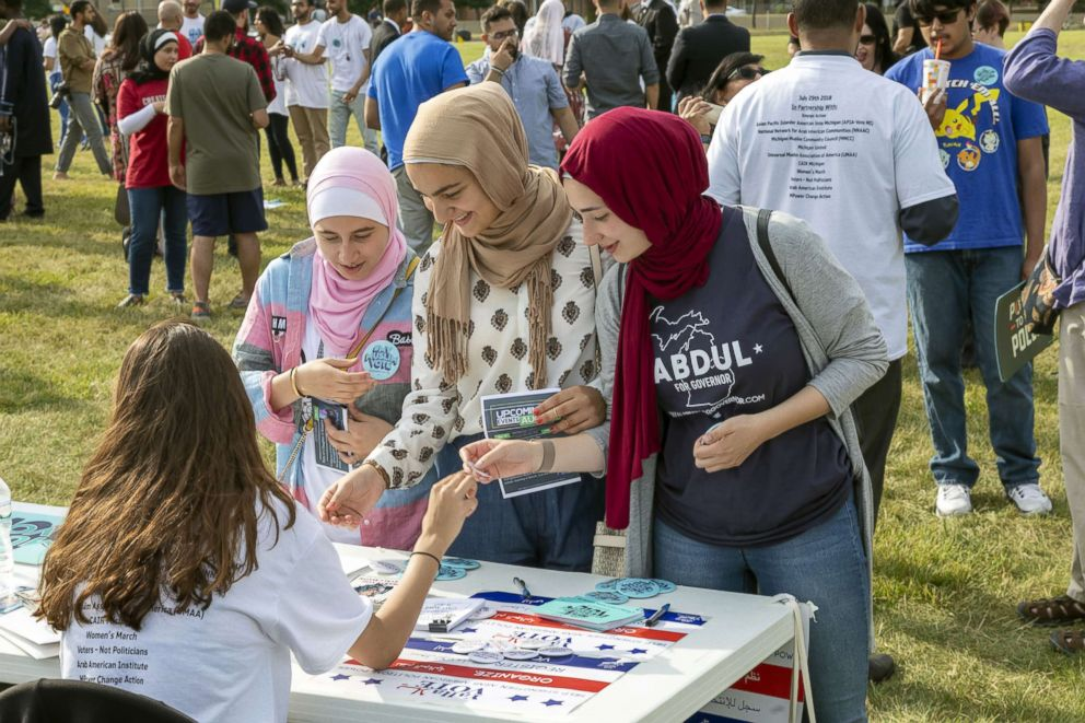 """Women pick up literature at a """"My Muslim Vote"""" rally in Dearborn, Mich., July 29, 2018."""