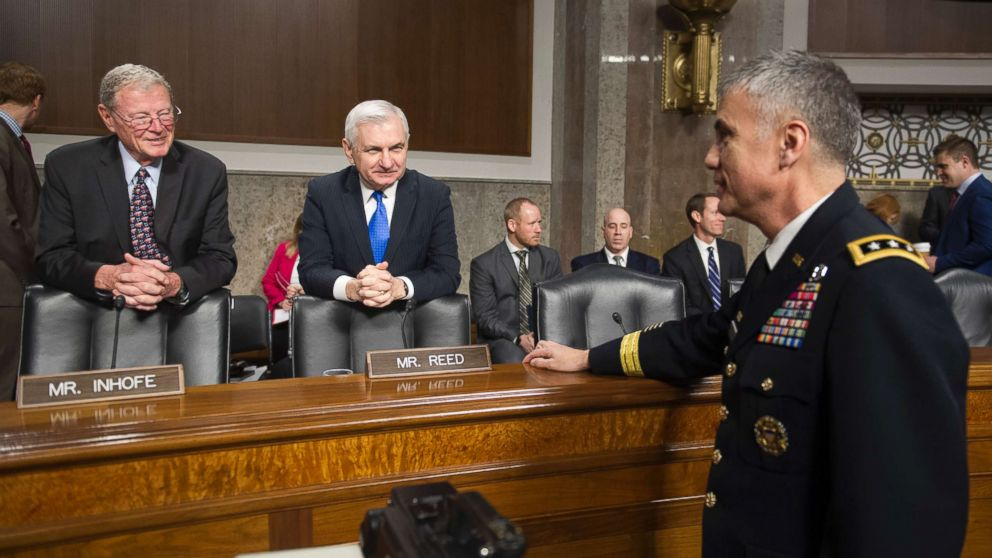 Army Lieutenant General Paul Nakasone, right, talks with Senate Armed Services Committee Chairman James Inhofe, R-Okla., left, and ranking member Sen. Jack Reed, D-R.I., at the start of the Committee's hearing to discuss Nakasone's qualifications as nominee to be National Security Agency Director and U.S. Cyber Command Commander, during a hearing on Capitol Hill in Washington, March 1, 2018.