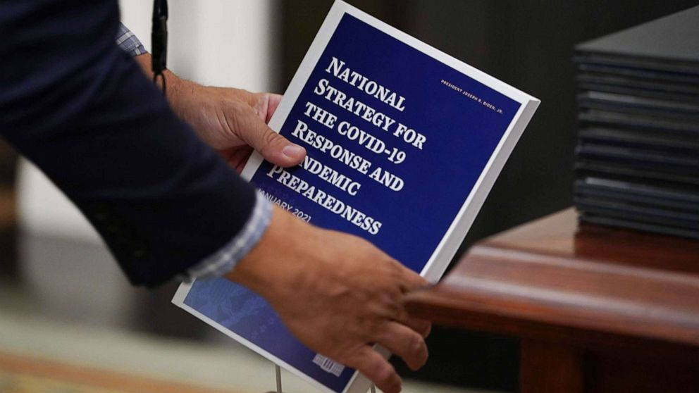 PHOTO: An aide collects copies of the National Strategy for COVID-19 before President Joe Biden speaks in the State Dining Room of the White House in Washington, Jan. 21, 2021.
