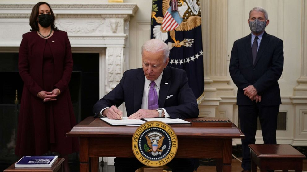 PHOTO: President Joe Biden signs executive orders as part of the COVID-19 response as Vice President Kamala Harris and Director of NIAID Anthony Fauci look on in the State Dining Room of the White House in Washington, D.C., Jan. 21, 2021.