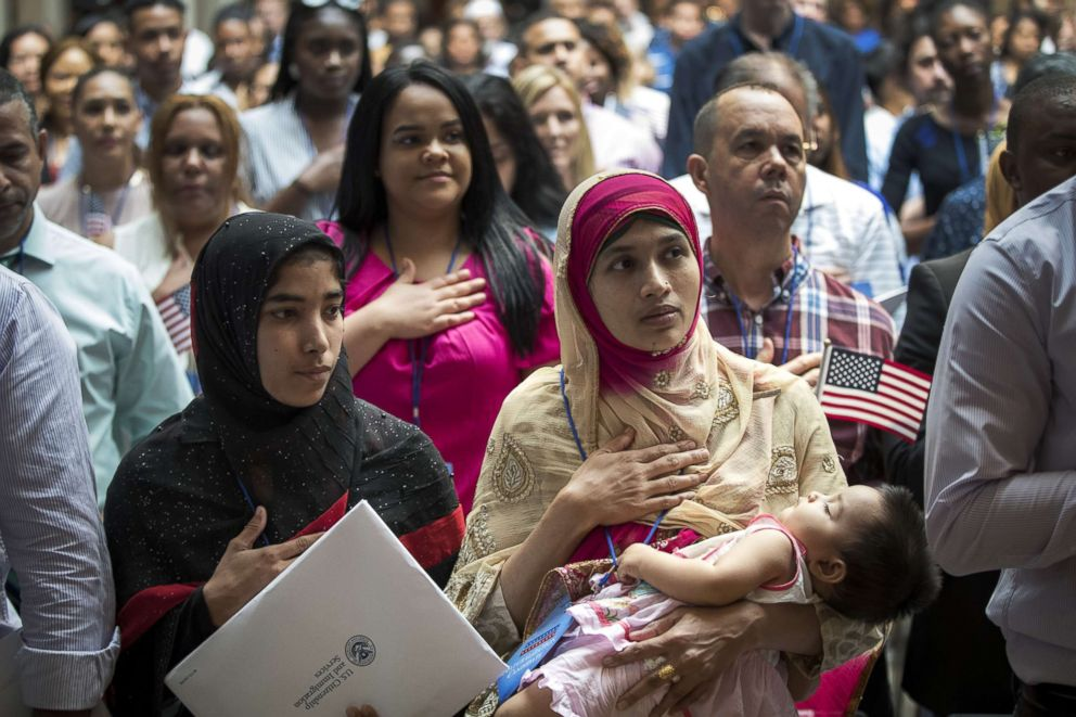 Mosammat Rasheda Akter, originally from Bangladesh, holds her 7 month-old daughter Fahmida as she recites the Pledge of Allegiance after officially becoming a U.S. citizen during a naturalization ceremony at the New York Public Library, July 3, 2018. 200 immigrants from 50 countries became citizens during the ceremony, one day before America's Independence Day.